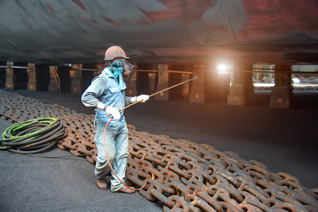 worker, paint man, working for repainting after sand blasting of the bottom layer of the commercial ship in floating dock yard by spraying paint machine