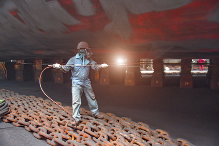 worker, paint man, working for repainting after sand blasting of the bottom layer of the commercial ship in floating dock yard by spraying paint machine Stock Photo