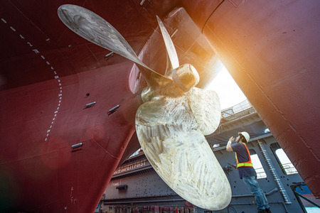 Stevedore, controller, Port Master, surveyor inspect theaft stern propeller of the ship in floating dry dock, recondition of overhaul repairing and painting, sand blasting in dry dock yard Reklamní fotografie