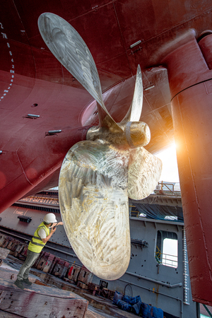 Stevedore, controller, Port Master, surveyor inspect theaft stern propeller of the ship in floating dry dock, recondition of overhaul repairing and painting, sand blasting in dry dock yard Фото со стока