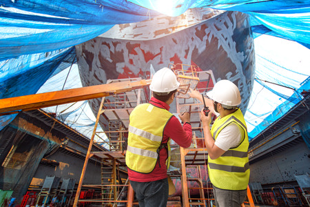 Stevedore, controller, Port Master, surveyor inspect the bulk head of commercial cargo ship in floating dry dock, recondition of overhaul repairing and painting, sand blasting in dry dock yard