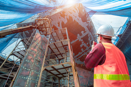 engineering or worker, motor man, loading master or controller working in communication by walkie talkie to team for safety loading winch of the crane, lifting gear operation in industrial at work Stock Photo