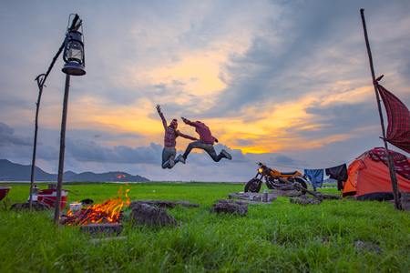 couple lover enjoy camping in jumping freedom, countryside traveling of the couple lover, campfire enjoying 免版税图像
