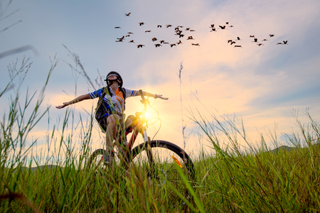 Woman cyclist bicycle cheerfully riding on the way of meadow field, adventure woman riding mountain bike alone in meadow at countryside