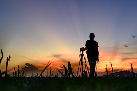 woman photographer enjoy with the sacenery view of sunset at field of meadow