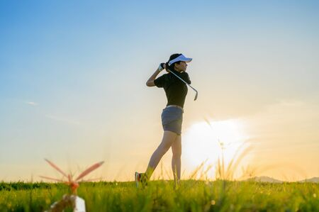 woman golf player in action setup after hit the golf ball away from fairway to the destination green off, fairway at light of sunset