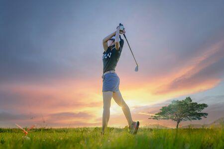 Joueuse de golf en action adresse de configuration après avoir frappé la balle de golf loin du fairway vers le green de destination, fairway à la lumière du coucher du soleil en arrière-plan Banque d'images