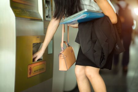 hand of working woman takes ticket card in machine slot, going to destination by ticket train or bus by auto teller machine buying 写真素材