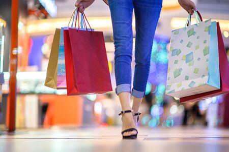 benen van vrouw blij en vrolijk in winkelcentrum, kopen en winkelen consumentisme met veel tassen in beide handen
