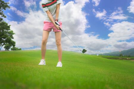 woman golf player in action hit the golf ball away from fairway to the destination green at day light sky