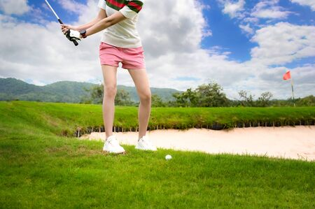 woman golf player concentrate in hit the golf ball cross over the hitch or obstacle of sand rub, cross over or sort out the trouble problem ahead, reach destination on green for winning in score rate Foto de archivo