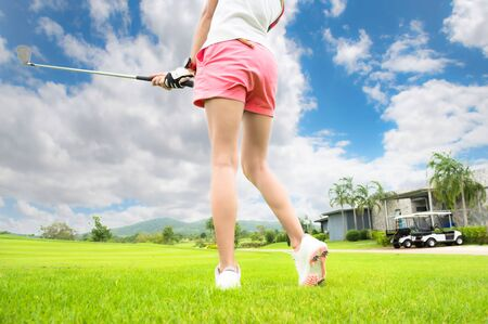 back of woman golf player concentrate in hit or chip the golf ball away to the destination on green for winning in score rate