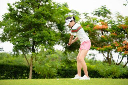 Joueur de golf femme en action en cours de configuration pour frapper la balle de golf loin du rugueux du fairway jusqu'au green de destination