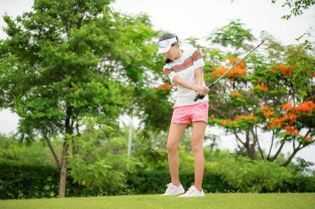 Une joueuse de golf se concentre pour frapper la balle de golf vers le green de destination pour gagner en taux de score
