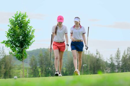 young asian woman golf players walking together on the green, enjoy playing golf competitor in fairway, golfmate playing together hapiness Banco de Imagens