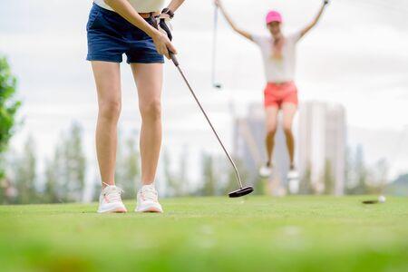 junge Golfspielerin versäumte es, den Golfball auf dem Grün des Golfplatzes in das Loch zu stecken, fröhlich und glücklich über das Versagen des gegnerischen Konkurrenten im Hintergrund Standard-Bild