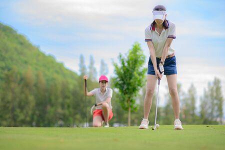 joueuse de golf en action en cours de configuration adresse au swing arrière pour frapper la balle de golf loin de T-OFF vers la destination sur le green, fairway au ciel clair du jour, PAR 3 T OFF