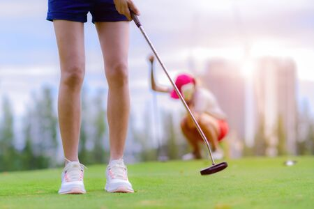 young woman golf player success to putting golf ball into the hole on the green of the golf course, upset and disaster of the opponent competitor acting in background Banco de Imagens
