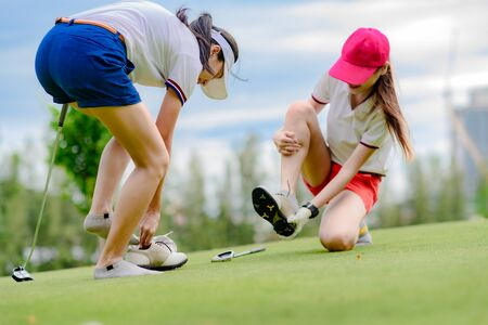 young woman golf player feel uncomfortable in wear of golf shoe, change or replace active shoe in the golf course, dissatisfied golf shoe during playing in golf course