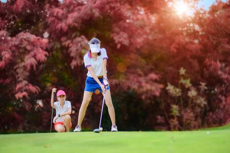 young woman golf player in action being setup address to hit the golf ball away from T-OFF to the destination green fairway, concentrate setup address to hit the ball away