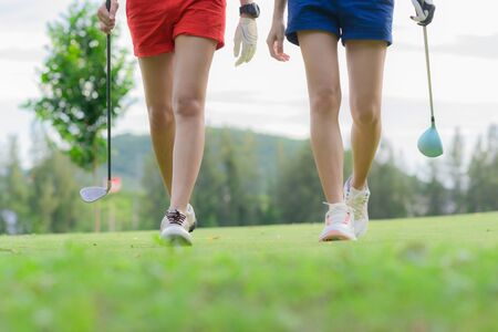 young golf players both walking to the fairway after hit the ball from T-OFF, next shot going to takes on the fairway hit to the green