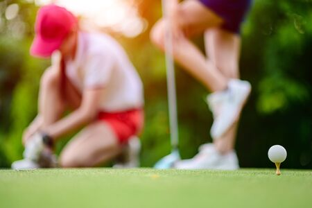golf ball stansing on wooden TEE ready to serving hit by the golfer on the T-OFF, woman golf players are in relax feeling before goiong to hot to ball to fairway in sunny day Banco de Imagens