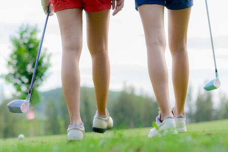 legs of young woman golf players both walking to T-OFF to take next shot hit the ball to the destination fairway
