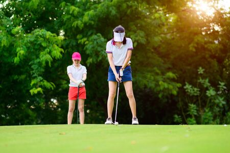 woman golf player in action being prepare and setup address to hit the golf ball away from T-OFF to destination fairway, PAR 3 attending, golf buddy or opponent waiting T-OFF in background