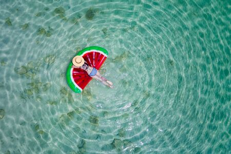 top aerial view of young woman enjoy swimming on floating inflatable tube in sea and cleared water, happy in summertime and vacation or long weekend swimming at sea