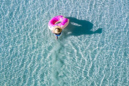 top aerial view of young woman enjoy swimming on holding floating inflatable tube to sea with cleared water, happy in summertime and vacation or long weekend swimming at sea 版權商用圖片