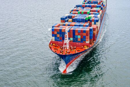top aerial view of the large volume of TEU containers on ship sailing in the sea carriage the shipment from loading port to destination discharging port, transport and logistics services to worldwide Stock fotó