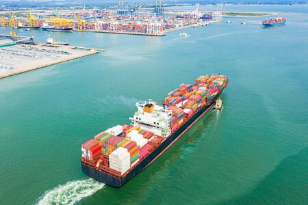 top aerial view of the large TEU containers ship arrival to the port, carriage the shipment from loading port to destination discharging port, transport and logistics services to worldwide