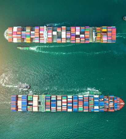 top aerial view of the large volume of TEU containers ships sailing cross over each other in the sea, carriage the shipment from loading port to destination discharging port, transport and logistic service to worldwide