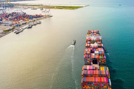 top aerial view of the large TEU containers ships arrival and departure the port, carriage the shipment from loading port to destination discharging port, transport and logistics service to worldwide