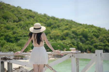 young woman standing on wooden bridge, enjoy the sea beach mountain in summer vacation and long holidays, tourist in island travel