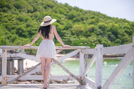 young woman standing on wooden bridge, enjoy the sea beach in summer vacation and long holidays, tourist in island travel