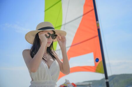 young woman enjoy with sailing boat in the sea with blur bright sky, island traveling Stock fotó