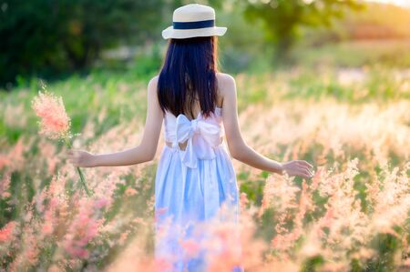 young woman walks feel freedom in the light of warm sun, bloom of wild flower in meadow, enjoyment and peaceful in the field of meadow