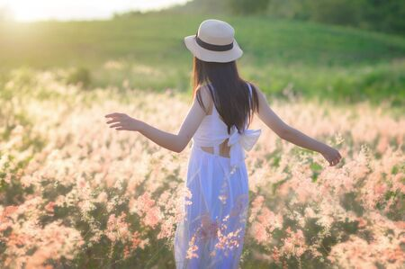 young woman walks feel freedom in the light of warm sun, bloom of wild flowers in meadow, enjoyment and peaceful in the field of meadow