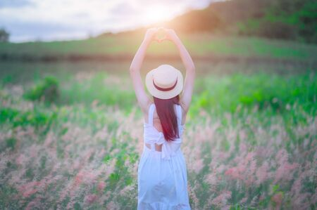 young woman walks feel freedom and create gesture hand in heart symbol up in the air, the light of warm sun, bloom of wild flowers in meadow, enjoyment and peaceful in the field of meadow Stock fotó
