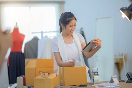 woman tailor made packing goods into boxes containers, ready to delivery to customer under address inform online device Stock fotó