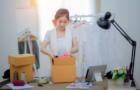 woman working alone in packing goods into boxes containers, ready to delivery to customer under rush at order and services, in time delivery by courier serving