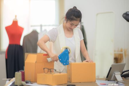 woman tailor made packing goods into boxes containers, ready to delivery to customer