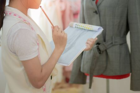 young woman fashion designer or tailor made at work with cloth fabric. Professional tailor in creative style and character designs modelling