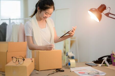happy woman tailor made packing goods into boxes containers, ready to delivery to customer under address inform online device Stock fotó