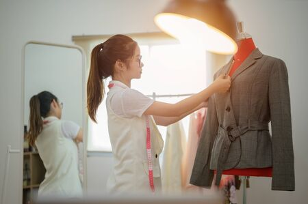 woman fashion designer at work with cloth fabric. Professional tailor measuring textile material. Female at work with measuring tape for exactly size intention Stock fotó