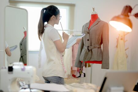 woman tailor made or fashion designer at work with cloth fabric. Professional tailor concentrate in creative style of fabric character