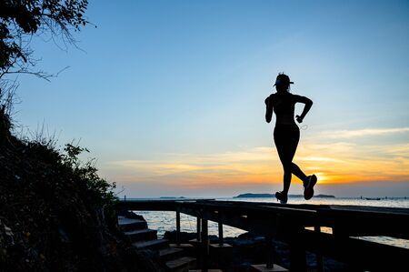 silhouette of sport woman in practice of exercise on wooden bridge at sunset, enjoy music while workout on the pier jetty in the sea Stock fotó