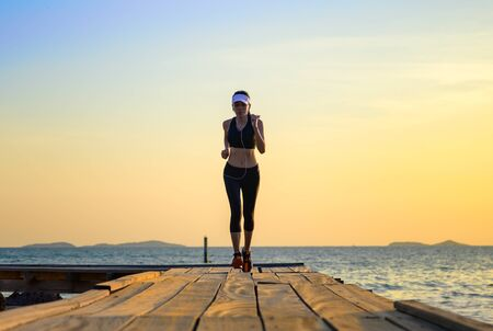 sport woman in running trail on wooden bridge at sunset, enjoy music while workout on the pier jetty in the sea Stock fotó