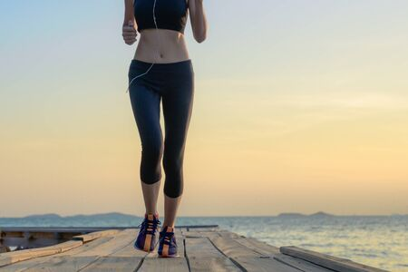 legs of healthy woman jogging alone at daily morning on the wooden jetty bridge or pier, daily exercise workout running at light of sunset, trail running at seaside